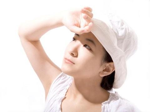 手で日光を遮る白い帽子をかぶった女性