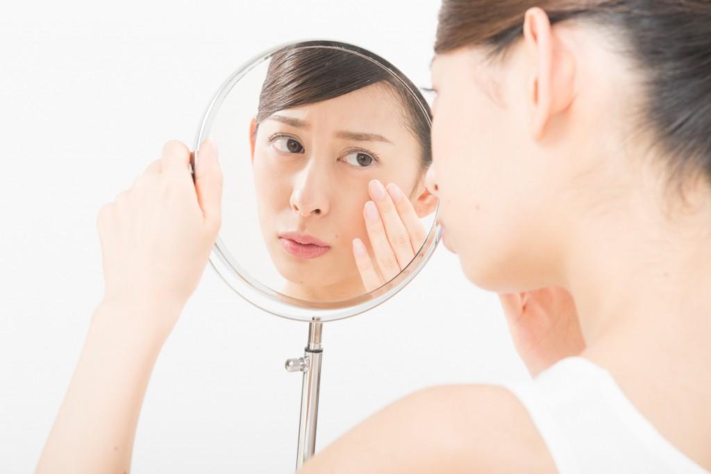 シミ・くすみを鏡で見る女性